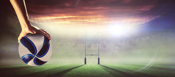 Composite image of rugby player with arm raised holding ball Royalty Free Stock Photography