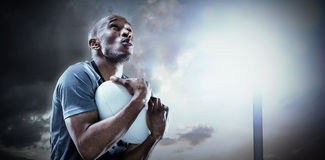 Composite image of rugby player catching ball while playing Royalty Free Stock Photography