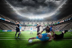 Composite image of rugby player doing a drop kick. Rugby player doing a drop kick against rugby stadium Royalty Free Stock Image
