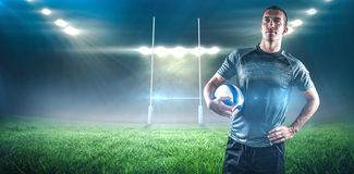 Composite image of rugby player holding ball with hand on hip Stock Photos