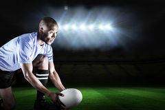 Composite image of rugby player looking away while keeping ball on kicking tee Royalty Free Stock Images