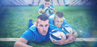 Composite image of rugby player looking away while lying in front with ball Stock Photography