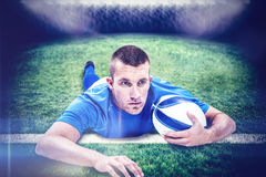 Composite image of rugby player looking away while lying in front with ball Royalty Free Stock Photo