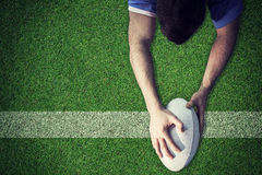 Composite image of a rugby player scoring a try. A rugby player scoring a try against pitch with line Royalty Free Stock Image