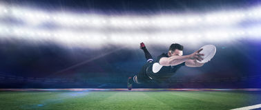 Composite image of rugby player scoring a try. Rugby player scoring a try against rugby stadium royalty free stock image