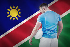 Composite image of rugby player standing with ball Royalty Free Stock Photo