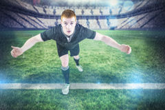 Composite image of rugby player tackling the opponent. Rugby player tackling the opponent against rugby pitch Royalty Free Stock Photos