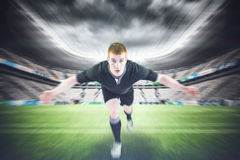 Composite image of rugby player tackling the opponent Stock Photography