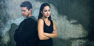 Composite image of sad couple with arms crossed standing back to back. Sad couple with arms crossed standing back to back against rusty weathered wall Royalty Free Stock Image