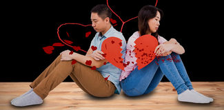 Composite image of sad couple holding broken heart pieces Royalty Free Stock Image
