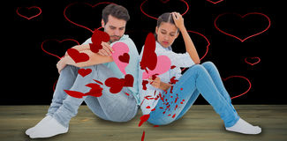 Composite image of sad couple sitting holding two halves of broken heart Stock Illustration