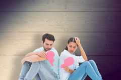 Composite image of sad couple sitting holding two halves of broken heart Royalty Free Stock Images