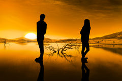 Composite image of sad couple standing back to back Stock Photos