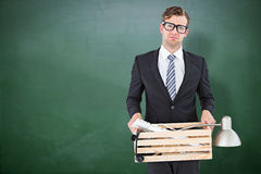 Composite image of sad geeky businessman holding box of his things Royalty Free Stock Images