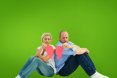 Composite image of sad mature couple holding a broken heart Royalty Free Stock Image