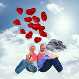 Composite image of sad mature couple holding a broken heart Royalty Free Stock Photography