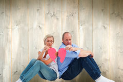 Composite image of sad mature couple holding a broken heart Royalty Free Stock Images