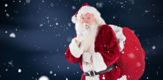 Composite image of santa asking for quiet with bag Stock Photo