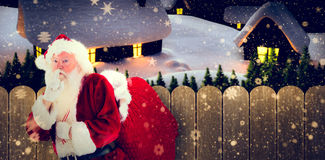 Composite image of santa asking for quiet with bag Royalty Free Stock Image