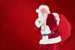 Composite image of santa asking for quiet with bag Royalty Free Stock Photo