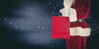 Composite image of santa carries red gift bag Royalty Free Stock Photo