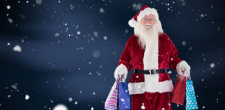 Composite image of santa carries some christmas bags. Santa carries some Christmas bags against blue sky with clouds stock photography