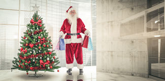 Composite image of santa carries some christmas bags. Santa carries some Christmas bags against home with christmas tree stock photos