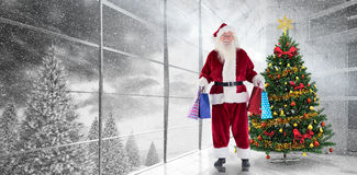 Composite image of santa carries some christmas bags. Santa carries some Christmas bags against home with christmas tree royalty free stock images