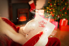 Composite image of santa checking his list Royalty Free Stock Images