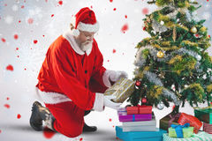 Composite image of santa claus arranging presents near christmas tree Royalty Free Stock Image