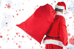 Composite image of santa claus carrying red bag full of gifts Royalty Free Stock Photography