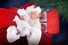 Composite image of santa claus carrying sack Royalty Free Stock Photos