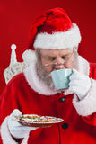 Composite image of santa claus drinking coffee with cookies Royalty Free Stock Photos