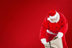 Composite image of santa claus filling gift boxes in sack Royalty Free Stock Photo