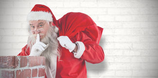 Composite image of santa claus with finger on lips standing beside chimney. Santa Claus with finger on lips standing beside chimney against white wall Royalty Free Stock Image