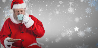 Composite image of santa claus having coffee with cookies stock images