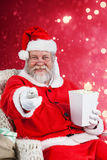 Composite image of santa claus having popcorn while watching tv. Santa Claus having popcorn while watching TV against light design shimmering on red Royalty Free Stock Photography