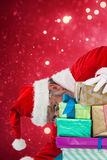 Composite image of santa claus hiding behind christmas gifts Stock Photos