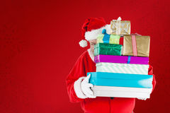 Composite image of santa claus hiding behind christmas presents Stock Photo