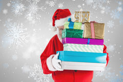 Composite image of santa claus hiding behind christmas presents Stock Photos