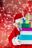 Composite image of santa claus hiding behind stack christmas gifts Royalty Free Stock Image