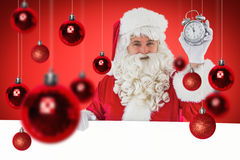 Composite image of santa claus holding alarm clock and sign Royalty Free Stock Photography
