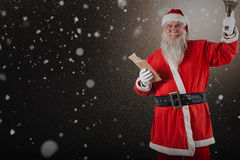 Composite image of santa claus holding bible and bell. Santa Claus holding bible and bell against snow Royalty Free Stock Images