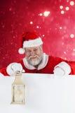 Composite image of santa claus holding christmas lantern Royalty Free Stock Photo