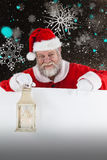Composite image of santa claus holding christmas lantern royalty free stock photo
