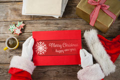 Composite image of santa claus holding a red placard. Santa claus holding a red placard against banner merry christmas Stock Photos