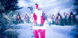 Composite image of santa claus holding ski and ski poles Stock Photography