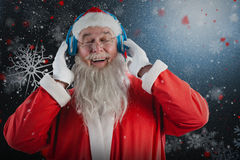Composite image of santa claus listening music on headphones. Santa Claus listening music on headphones against snowflake pattern Stock Photo