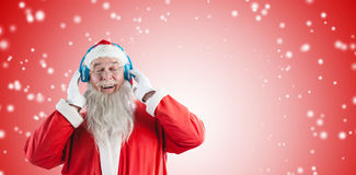 Composite image of santa claus listening music on headphones. Santa Claus listening music on headphones against white light dots on red Stock Photo