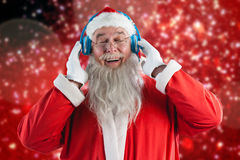 Composite image of santa claus listening music on headphones. Santa Claus listening music on headphones against white snow and stars on red Stock Photography